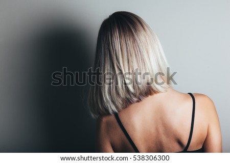 Model with unrecognizable face with blond shiny hair. Woman bob haircut styling. Back view.
