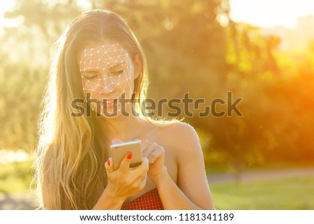 model woman long-haired in red dress holds phone and talking typing text with boyfriends in hand rays of sun background . enamored girl chating with friends in the park, concept face id #1181341189