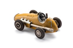 Model yellow toy vintage racing car in a side view showing the large exhaust over a white background with shadow