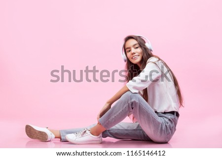 Stock Photo Model young trendy beautiful girl with natural make-up with headphones on a pink background fashion Studio shot