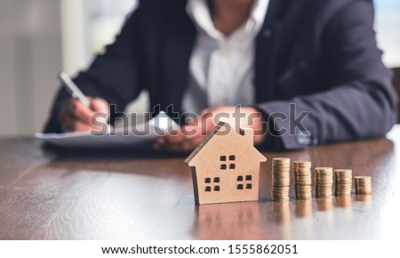 Modeling wooden houses and coins and dollars placed on wooden tables,preparation concept for house model purchase and the fastest growing real estate economy,moving home or renting property via agent Foto stock ©