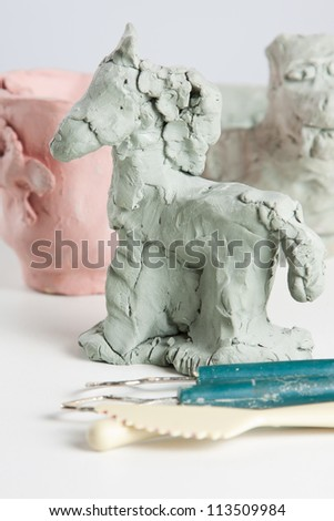 Modelling a horse from clay or plasticine in a creative craft class with sculpting tools in the foreground