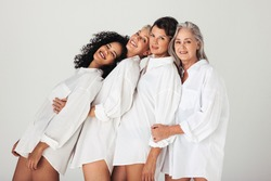 Models of different ages embracing their natural and aging bodies in a studio. Four confident and happy women smiling cheerfully while wearing mens shirts against a white background.