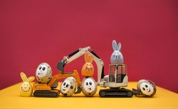 models of toy excavators, Easter bunnies, quail eggs with painted smiles and eyes. Business congratulations concept for construction companies. postcard. copy space