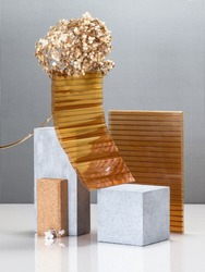 Modern abstract still life using concrete blocks, building construction elements and a golden plant.