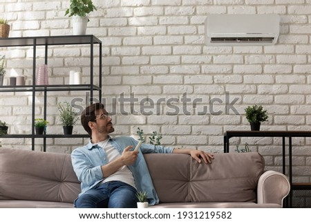 Modern ac is my choice. Happy male owner of new apartment sit on couch at home hold remote controller set comfy temperature on air conditioner. Young man control climate indoors enjoy fresh cool air