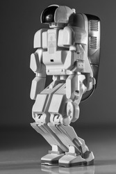 Modern advanced autonomous robot toy isolated on a gray background.