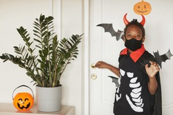 Modern African American boy wearing devil costume with red horns and black mask on face saying bye to his parents and going to trick or treat with friends..