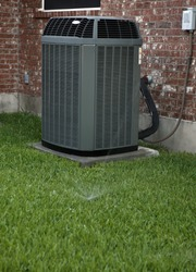 Modern air conditioner on backyard with working sprinkler system