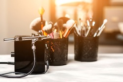 Modern airbrush and tools for professional makeup. Make-up products set. Beauty studio background. Cosmetics and brushes on artist workplace