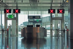 Modern airport departure check in gates closed with red X signs above and an aircraft on the runway.