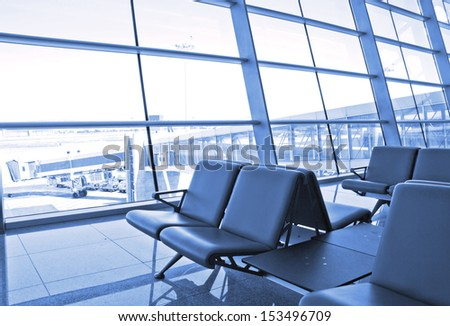 modern airport terminal waiting room with window outside scene of flight departure