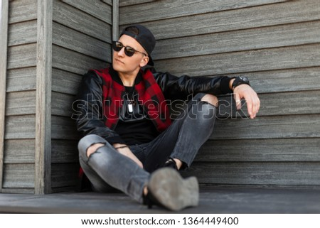 Modern American handsome young hipster man in stylish clothes in a stylish black baseball cap in trendy sunglasses sits and enjoys a warm summer day. Attractive guy model relaxes. Men's youth fashion.