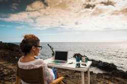Modern and alternative lifestyle office wokstation with free business woman at work in open office with scenic ocean view - freedom from usual job - digital nomad life