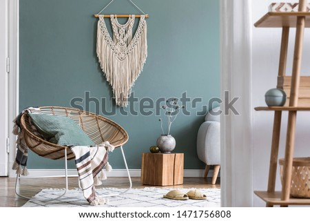 Modern and bohemian composition of interior design at apartment with rattan armchair, wooden cube, plaid, pillows, flowers, macrame, bamboo shelf and elegant accessories. Stylish home decor. Template.