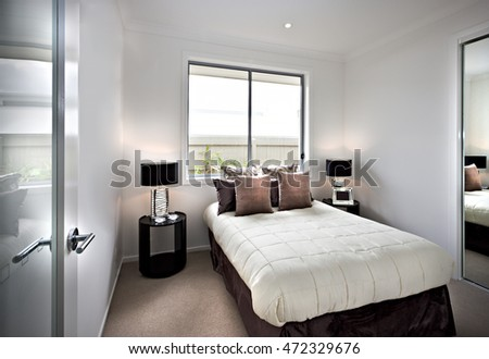 Modern and classic bedroom with windows and attractive  lamps near the glass panel and pillows on the mattress which surrounded by white walls #472329676