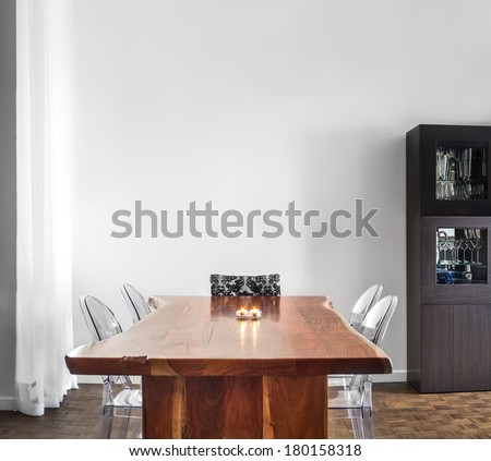 Modern and Contemporary dining room table and decorations with blank wall for your text, image or logo.