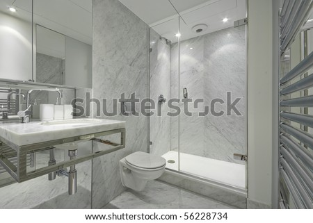 Modern and contemporary en suite bahroom in marble white with designer fragments, shower, stylish wash basin and toilet