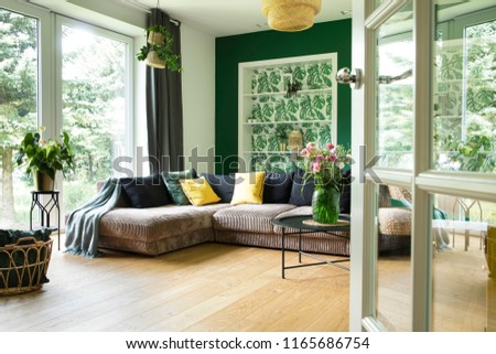 Modern and cozy living room with corduroy sofa, pillows, big window to the garden. Bright and sunny space.  #1165686754