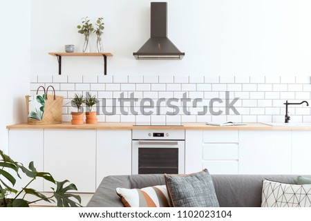Modern and design scandinavian kitchen with plants, accessories and straw bag. Sunny and bright space with white brick wall.