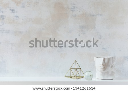 Modern and eclectic room interior with abstract wiped walls, gold pyramid and head sculpture .Stylish space with design accessories. Eclectic home decor. Real photo. Copy space for inscription.