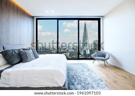 Modern and luxurious hotel bedroom with views of London skyline. Condo or 5-star upscale accommodation.