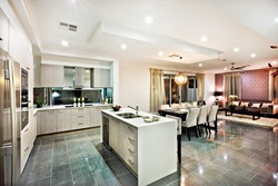 Modern and shiny kitchen with dining and living area, including a counter top and kitchenware on the reflective tiles, there are lights flashing at night