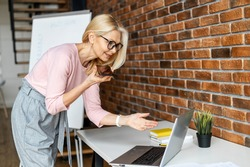 Modern and skilled middle-aged business woman looks at the laptop screen and recording a voicemail on the smartphone, female project manager makes a remark and sends to an executor