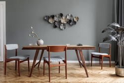 Modern and stylish dining room interior with glamour wooden table , elegant chairs and design decoration. Template. Home decor. Gray background wall. Minimalistic concept of interior design.