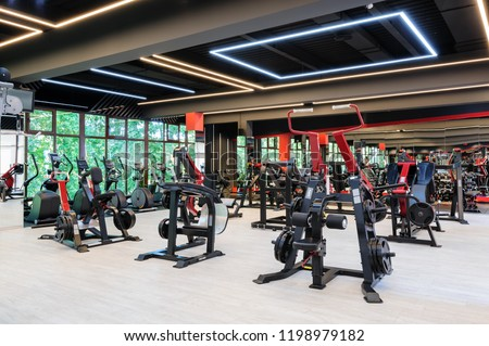 Modern and stylish gym interior with equipment, some motion blurred unrecognizable persons #1198979182