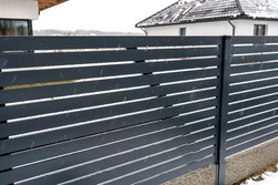 Modern anthracite panel fencing with a visible connector of the fence foundations, it rains in winter, in the background the roofs of the house with snow.