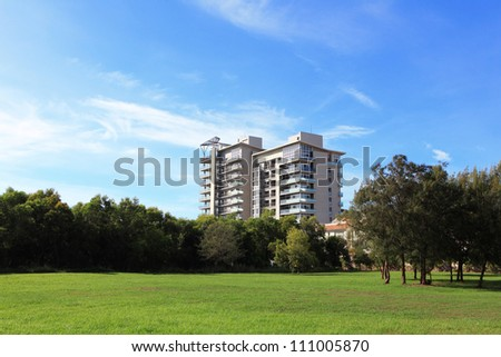 modern apartment building with green grass and blue sky