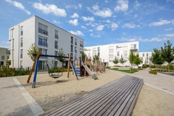 Modern apartment buildings in a green residential area with playground in the city
