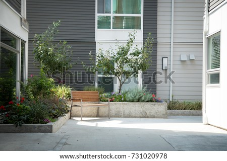 Modern apartment courtyard scene of a wood park bench beside a landscaped planter in morning light