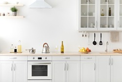 Modern apartment for sale and rent real estate, simply, scandinavian, minimalist interior. Kettle and utensils on white furniture, shelves with dishes and potted plant in daylight, empty space