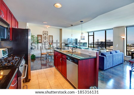 Modern apartment interior. Black and burgundy kitchen, bright living room with glass wall and old fashioned dining area