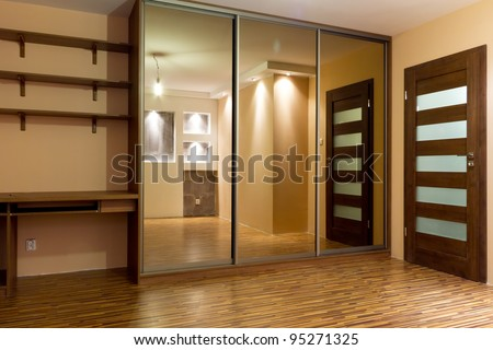 Modern apartment interior with huge wardrobe - stock photo