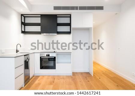 Modern apartment kitchen design with stone bench top and contrasty colour scheme. Australian interior design. #1442617241