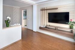 Modern apartment living room with large TV over wooden cabinet Orchid, cork floorboards and door to corridor. Real room of real estate residential house.
