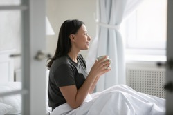 Modern apartment owner awakens enjoys good morning, start new day with cup of hot aromatic invigorating coffee, excellent mood, vacations concept. African woman wake up sit in bed holds mug drink tea