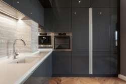 Modern apartment with contemporary interior at new kitchen. Built in household appliance, electric stove, oven, sink and water tap on white worktop