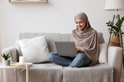 Modern arab girl in hijab using laptop at home, working remotely while sitting on couch in living room