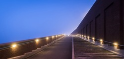 Modern architectural bridge and stairs on dike in Nijmegen over the Waal in the morning with fog, Netherlands.