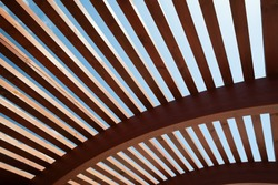 Modern architectural construction of wooden slats with half-round, openwork design