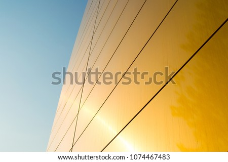 Modern architectural details. The facade is golden in color. Modern panel facade