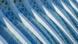 Modern architecture. Abstract pattern of shadows and light on curved diagonal lines of contemporary facade.Fragment of the facade of glass building.