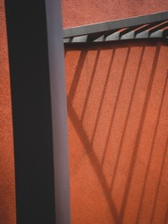 Modern architecture battens light and shadow effect pattern on a textured orange concrete wall. Selective focus. Blurred pillar foreground. Minimal background with copy space. Nakhon Nayok, Thailand.