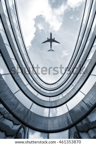 Modern architecture building with flying airplane in background. Low angle view blue colorized picture. #461353870