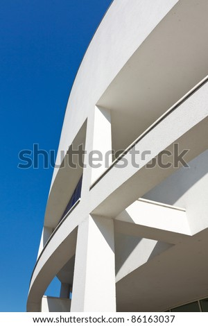 Modern architecture - curved white building against blue sky.
