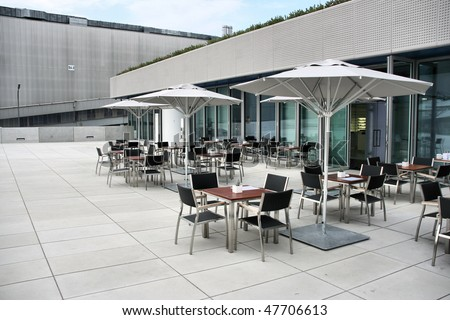 Modern architecture - fashionable outdoor cafe or restaurant tables in Munich, Germany